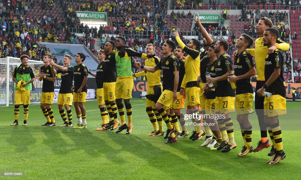 The team of Borussia Dortmund celebrate in front of the supporters after the German first division Bundesliga football match between FC Augsburg and Borussia Dortmund in Augsburg, southern Germany on September 30, 2017. / AFP PHOTO / Christof
