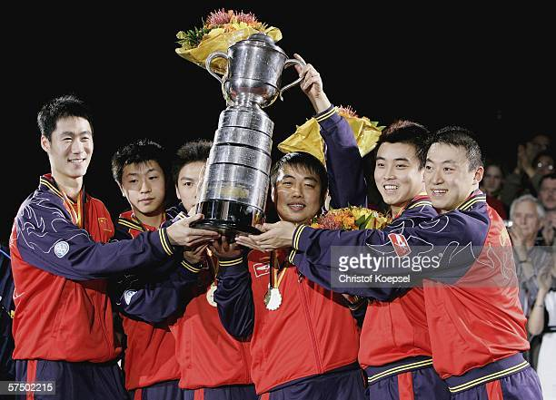 The team of China with Liqin Wang Long Ma Qi Chen head coach Liu Guoliang Hao Wang Lin Ma pose with the swaythling cup during the ceremony on the...