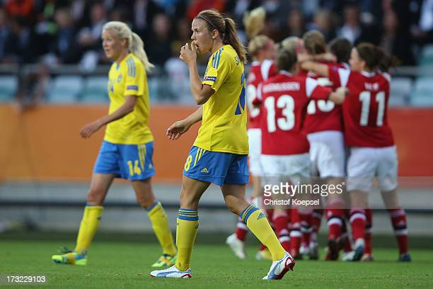 The team of Denmark celebrates the first gpoal and Josefine Oeqvist and Jessica Samuelsson of Sweden look dejected during the UEFA Women's EURO 2013...