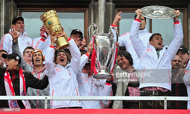 The team of FC Bayern Muenchen celebrates winning the Bundesliga Champions League and DFB Cup on the balcony of the cityhall on June 2 2013 in Munich...