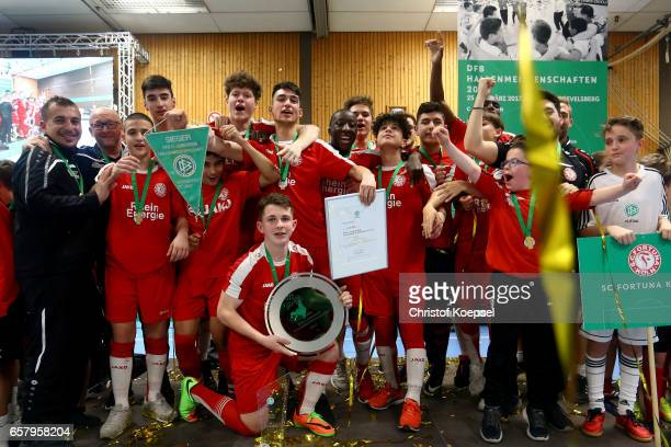 The team of Fortuna Koeln poses with the winning trophy of the C Juniors German Indoor Football Championship at Sporthalle West on March 26 2017 in...