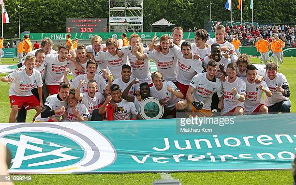 The team of Freiburg pose with the Cup after winning the DFB Juniors Cup final match between SC Freiburg and FC Schalke 04 at Stadion am Wurfplatz on...