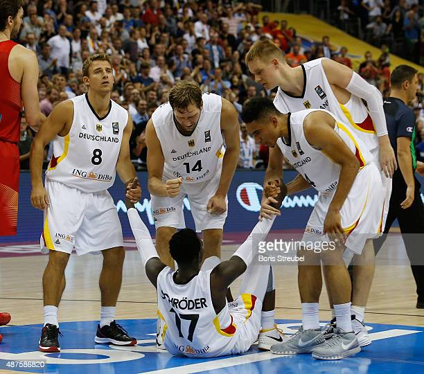 The team of Germany give team mate Dennis Schroeder a legup during the FIBA EuroBasket 2015 Group B basketball match between Germany and Spain at...