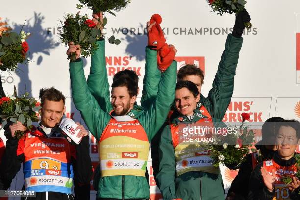 The team of Germany with Markus Eisenbichler and Richard Freitag celebrate next to Autria Daniel Huber during the flower ceremony after the men's...