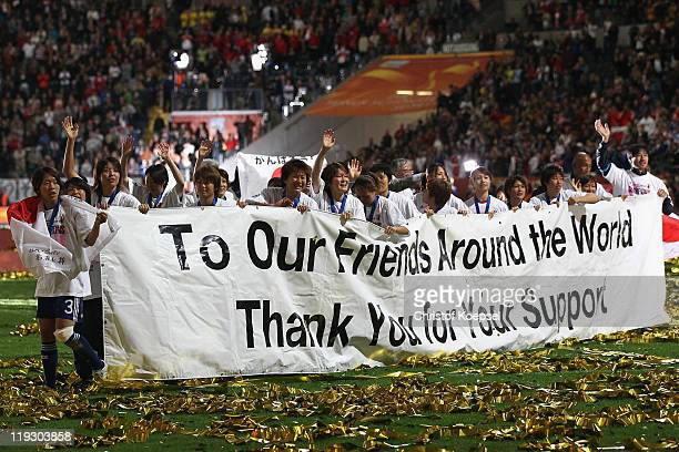 The team of Japan hold a banner after winning the FIFA Women's World Cup Final match between Japan and USA at the FIFA World Cup stadium Frankfurt on...