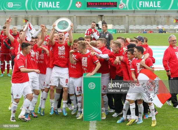 The team of Koeln pose with the cup after winning the DFB Juniors Cup final match between 1FC Kaiserslautern and 1FC Koeln at Stadion am Wurfplatz on...