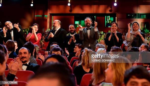 """The team of the Iranian film """"Sheytan vojud nadarad"""" applaud and react as they hear they are awarded with the trophy """"Golden Bear for Best Film""""..."""