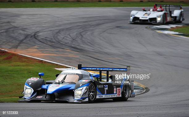 The Team Peugeot Total Peugeot 908 driven by Franck Montagny, Stephane Sarrazin leads the Audi Sport North America Audi R15 TDI of Lucas Luhr and...