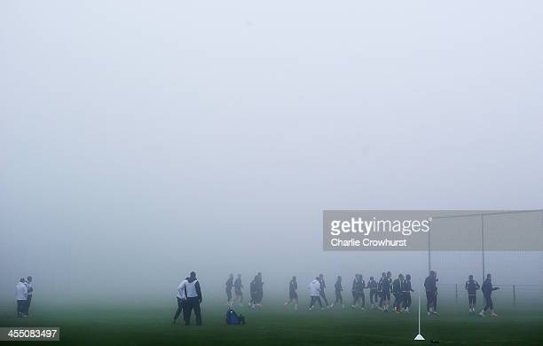 The team run through the warm up in the thick fog during Tottenham Hotspur training session ahead of their UEFA Europa League group match against FC...