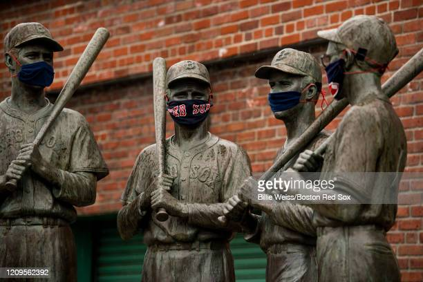 The Teammates statues of former Boston Red Sox players Ted Williams Bobby Doerr Johnny Pesky and Dom DiMaggio wear makeshift masks made of Red Sox...