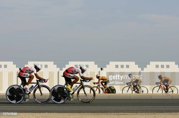 The teams from the United Arab Emirates and Mongolia pass each other on the road while they compete in the Men's Road Cycling Team Time Trial during...