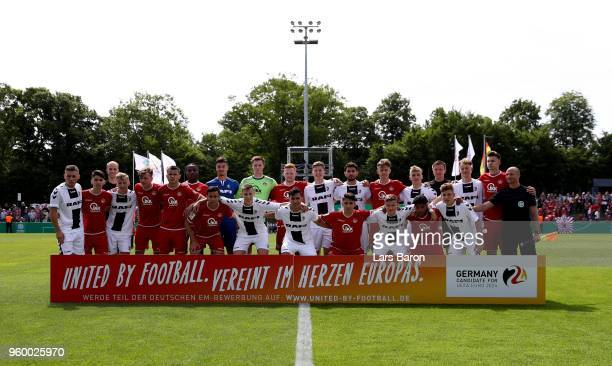 The teams line up behind a banner promoting the German bid for the UEFA European Championship 2024 prior to the DFB Juniors Cup Final 2018 between 1...