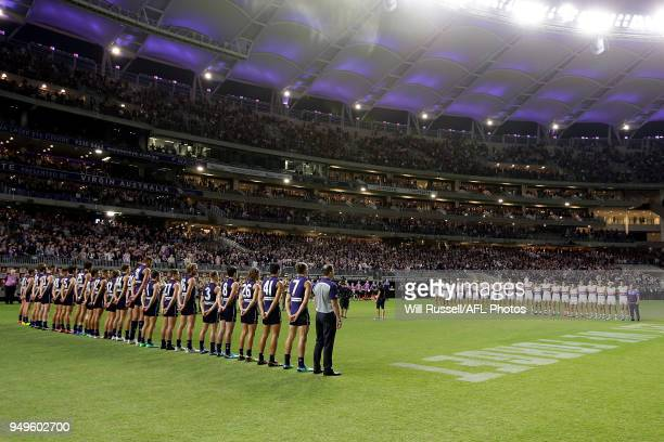 The teams line up for The Anzac proceedings during the round five AFL match between the Fremantle Dockers and the Western Bulldogs at Optus Stadium...