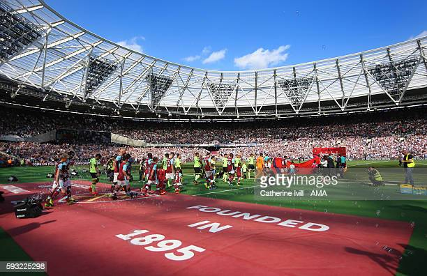 The teams make their way out onto he pitch for the first ever Premier League match at the stadium before the Premier League match between West Ham...