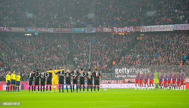 The teams of Muenchen and Leverkusen stand for a minute of silence for a young woman who was beaten to death when she tried to help other before the...
