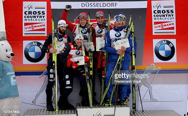 The teams of Norway Sweden and Italy celebrate on the podium after the 6 x 16 km free team sprint event at the FIS CrossCountry World Cup on December...