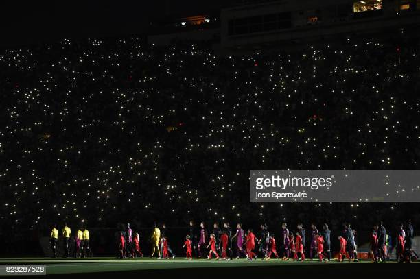The teams of Real Madrid and Manchester City take the field to a blacked out stadium as fans use the lights on their cell phones to illuminate the...