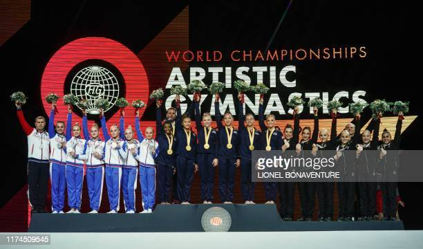 The teams of Russia the US and Italy celebrate on the podium after the women's team final at the FIG Artistic Gymnastics World Championships at the...