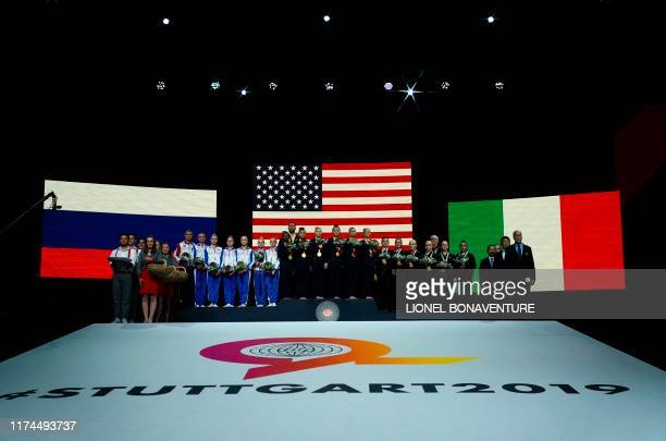 The teams of Russia the US and Italy pose after the women's team final at the FIG Artistic Gymnastics World Championships at the...