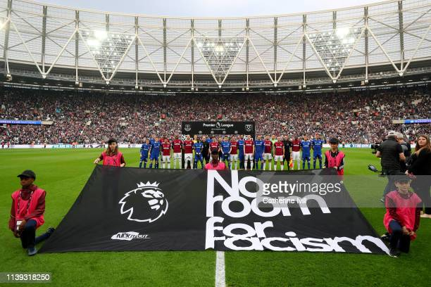 The teams pose behind a No Room for Racism sign ahead of the Premier League match between West Ham United and Everton FC at London Stadium on March...