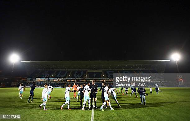 The teams shake hands with the referee with an empty stand behind them before the Checkatrade trophy match between Wycombe Wanderers and West Ham...