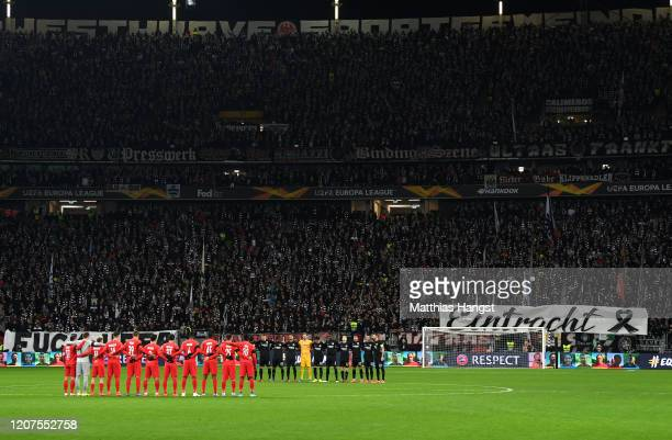 The teams stand for a minutes silence for the victims of the Hanau shootings prior to the UEFA Europa League round of 32 first leg match between...