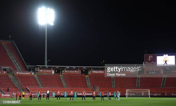 The teams stand for a minutes silence in memory of the victims of the Covid19 Pandemic prior to the La Liga match between RCD Mallorca and FC...