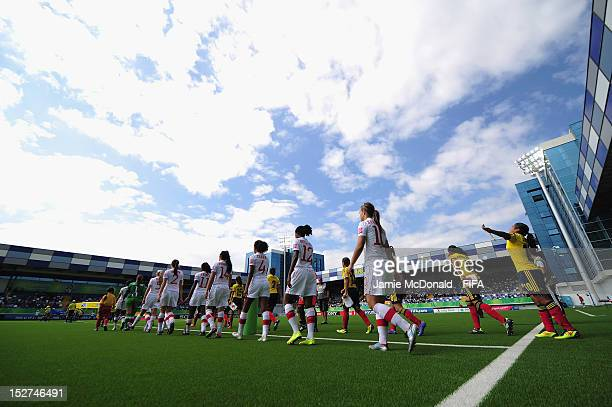 The teams walk onto the pitch during the FIFA U17 Women's World Cup 2012 Group A match between Columbia and Canada at Shafa Stadium on September 25...