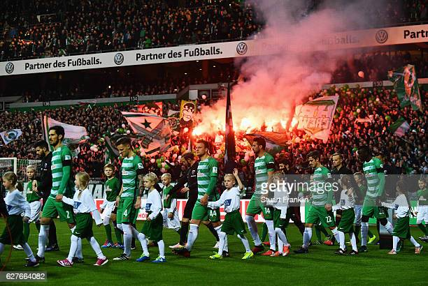 The teams walk out during the Bundesliga match between Werder Bremen and FC Ingolstadt 04 at Weserstadion on December 3 2016 in Bremen Germany