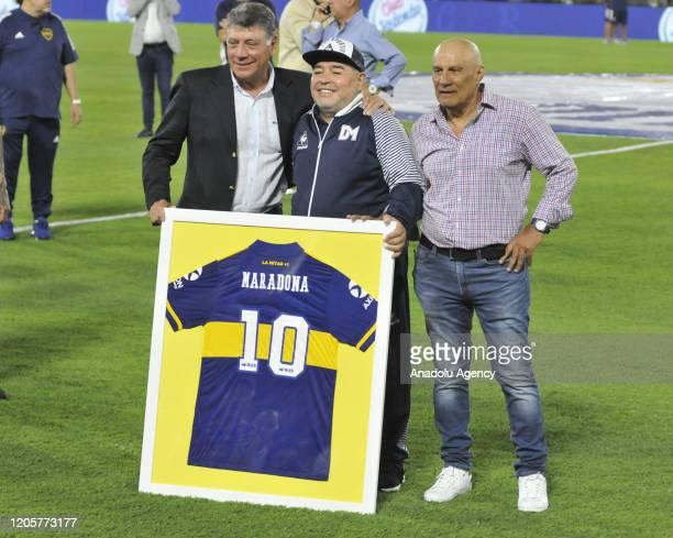 The technical director of Gimnasia y Esgrima La Plata Diego Armando Maradona receives a plaque from Miguel Angel Brindisi and Hugo Osmar Perotti...