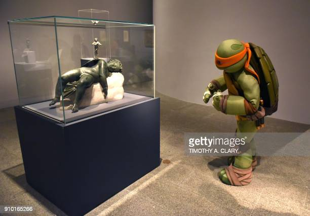TOPSHOT The Teenage Mutant Ninja Turtle Michelangelo aka Mikey visits the exhibition Michelangelo Divine Draftsman and Designer in his costume at the...