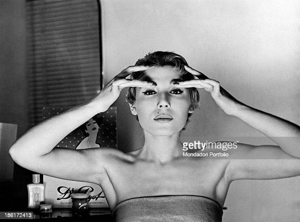 The television host Edy Campagnoli born Edda Campagnoli is posing in front of some beauty face creams she is rubbing a cream on her eyelids The host...