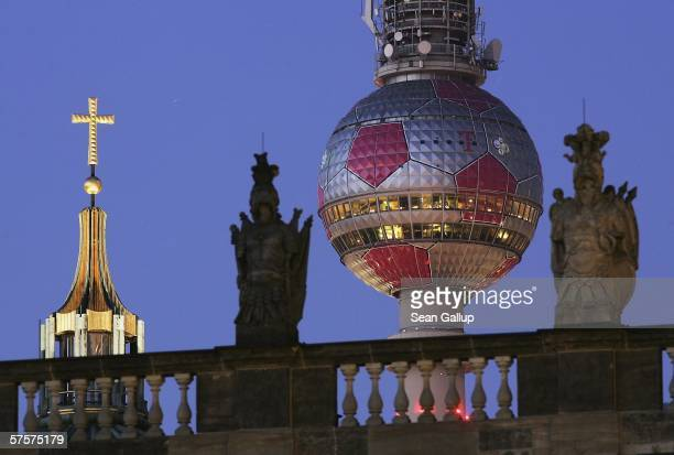 The television tower on Alexanderplatz with its sphere decorated like a giant soccer ball stands at twilight behind the Dom cathedral and the German...