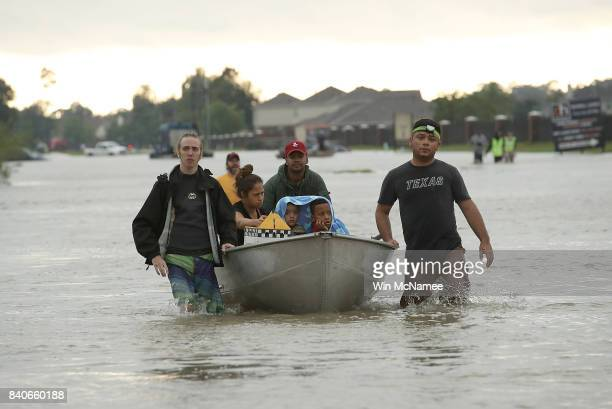The Tellez family is evacuated from their home after severe flooding following Hurricane Harvey in north Houston August 29 2017 in Houston Texas...