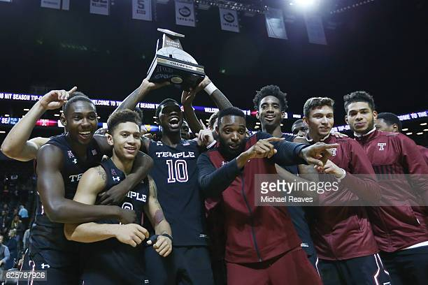 The Temple Owls celebrate with the trophy after defeating the West Virginia Mountaineers 8177 during the championship game of the NIT Season TipOff...