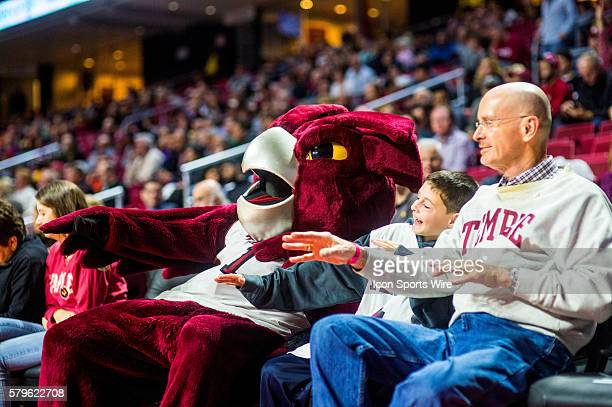 The Temple Owls mascot and a young fan heckle the Penn Quakers at the free throw line during the game between the Penn Quakers and the Temple Owls...