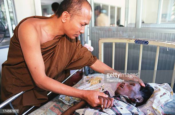 The temple's abbot Phra Alongkod comforts patients with AIDS at Wat Phra Baat Nam Phru Temple The majority of the monks here have AIDS Patients and...