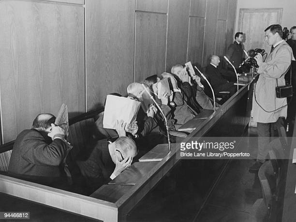 The ten defendants in the 'Treblinka Trial' for Nazi war crimes hide their faces from photographers and cameraman as they await the start of legal...