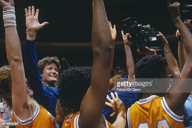 The Tennessee Lady Vols raise their arms in triumph with coach Pat Summit after winning the Final Four game against Long Beach State during the...