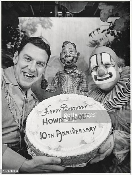 The tenth anniversary cake of the Howdy Doody Show is displayed by the show's stars Buffalo Bob Smith Howdy Doody and Clarabell the Clown