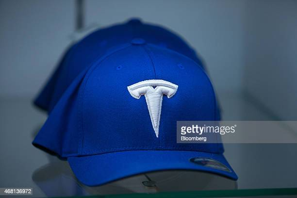 The Tesla logo sits on a baseball cap inside the Tesla Motors Inc store in Munich Germany on Monday March 30 2015 Chief Executive Officer Elon Musk...
