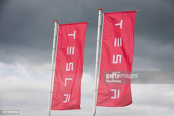 The Tesla logo sits on banners flying outside the Tesla Motors Inc factory in Tilburg Netherlands on Thursday Oct 8 2015 Tesla said it delivered...