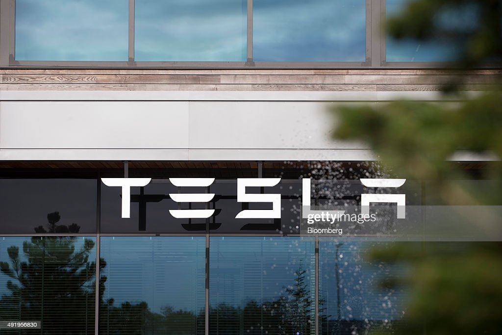 The Tesla logo sits on the exterior of the Tesla Motors Inc. factory in Tilburg, Netherlands, on Thursday, Oct. 8, 2015. Tesla said it delivered 11,580 vehicles in the third quarter, meeting its target after Chief Executive Officer Elon Musk handed over the first Model X sport utility vehicles just before the end of the period. Photographer: Jasper Juinen/Bloomberg via Getty Images