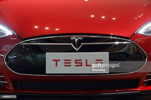 The Tesla Motors Inc badge and logo are seen below the hood of the Model S electric vehicle displayed at the company's showroom in Beijing China on...