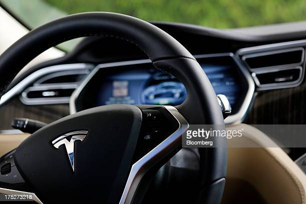 The Tesla Motors Inc logo is seen on the steering wheel of the Model S vehicle at company's design studio in Hawthorne California US on Wednesday...