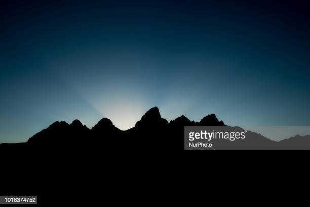 The Teton Range a mountain range of the Rocky Mountains is seen as the sun sets from Moose Wyoming United States at the Teton Point Turnout on July...