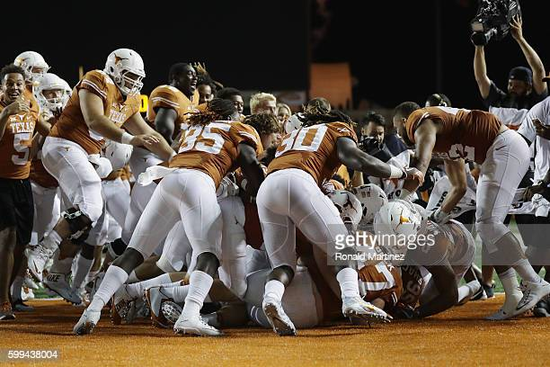The Texas Longhorns celebrate defeating the Notre Dame Fighting Irish 50-47 in a second overtime at Darrell K. Royal-Texas Memorial Stadium on...