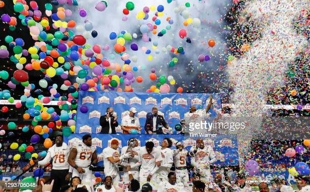 The Texas Longhorns celebrate during the trophy presentation after defeating the Colorado Buffaloes during the Valero Alamo Bowl at the Alamodome on...