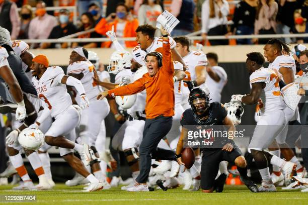 The Texas Longhorns celebrate their upset victory as quarterback Spencer Sanders of the Oklahoma State Cowboys reacts after getting taken down on the...