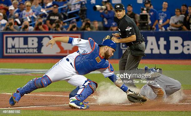 The Texas Rangers' Delino DeShields right scores on a single by teammate Adrian Beltre in the third inning as Toronto Blue Jays catcher Russell...